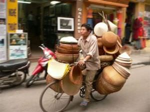 Vietnam local riding bicycle carrying stacks of hats