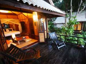 Ko Lanta hotel room with bed and sitting area on terrace