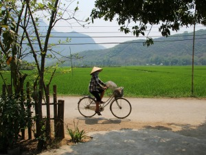 Locals cycle in Mai Chau, Laos