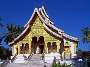 Green and gold Laotian temple surrounded by palm trees and blue sky