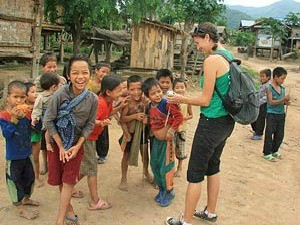 Woman laughing with local children in Laos