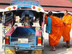 two monks next to a tuk-tuk
