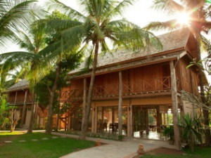 Laos wooden hotel on stilts with palm trees