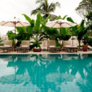 Laos hotel outdoor pool with lounge chairs and umbrellas