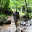 Man standing in shallow river whilst on a walk through Endau Rompin jungle