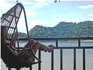 malaysia customer relaxing in hanging chair by the water