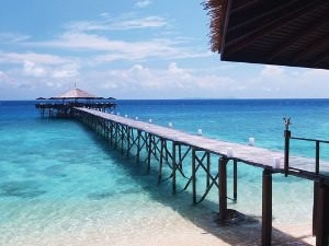 Malaysia long wooden boardwalk out to bungalow in turquoise water
