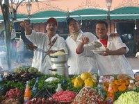 Food stall in Marrakesh with local Moroccans standing behind