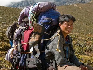 Nepal Porter sitting with a big bag of belongings on his back in the Nepal valley