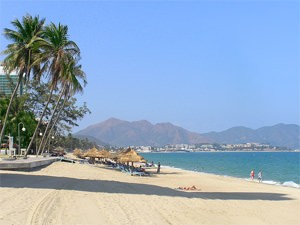 Nha Trang white sand beach with palm trees and mountains in distance