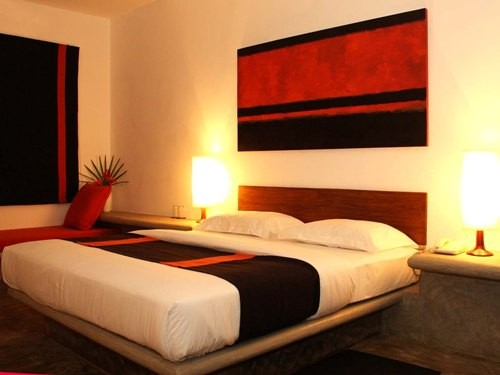 Cozy room with double bed and red paintings