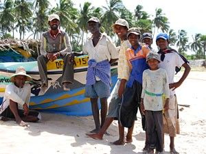 Local men and children leaning on a boat at the beach