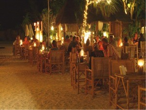 People having dinner in an outdoor restaurant at the beach