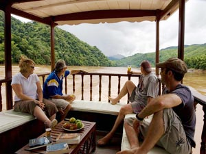 Group of customers on a boat looking out onto the Mekong river