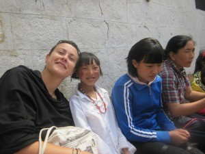 woman smiling with local children at school for the blind in tibet
