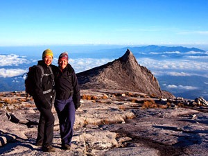 Trekking couple resting at the top of Mount Kinabalu in Borneo