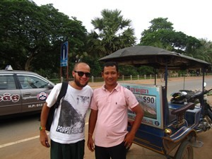 Man standing next to tuk tuk driver