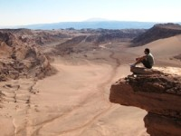 Man sitting on a stone ledge overlooking the Atacama Desert
