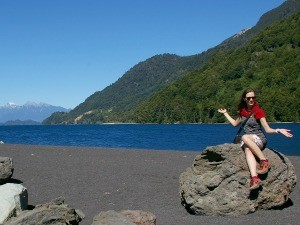 Staff member Jennifer sitting on a rock in Puerto Varas, Chile