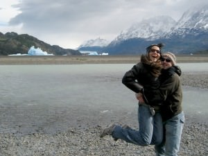Couple jumping in front of glacier