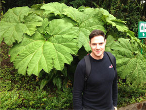 man standing in front of giant leaves