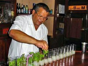 local barman making row of mojitos in cuba