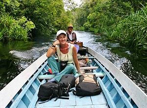 Woman riding a boat through jungle