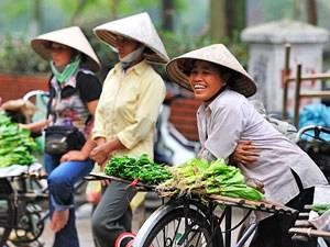 Vietnam locals smiling with bicycles and fruit for sale