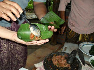 hands making food wrapped in banana leaves in indonesia