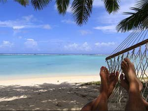 View of a person's feet lying in a hammock on the sandy beach in Indonesia