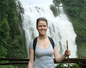 Laos woman smiling in front of waterfalls