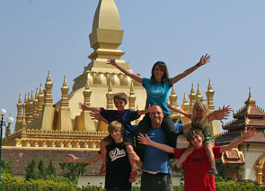 laos family smiling in front of temples