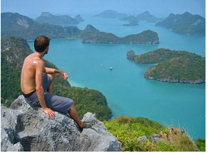 A man sitting on a rock overlooking Perhentian Islands in Malaysia