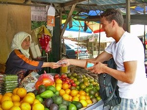 Malaysia customer purchasing fruit from local market stall