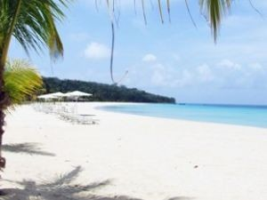 View across sandy white beach and blue water off Corn Island Nicaragua