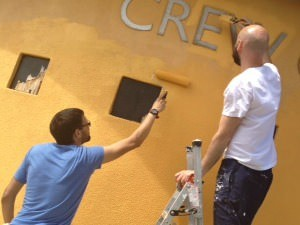 staff painting yellow building