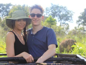 Couple smiling with elephant in the background