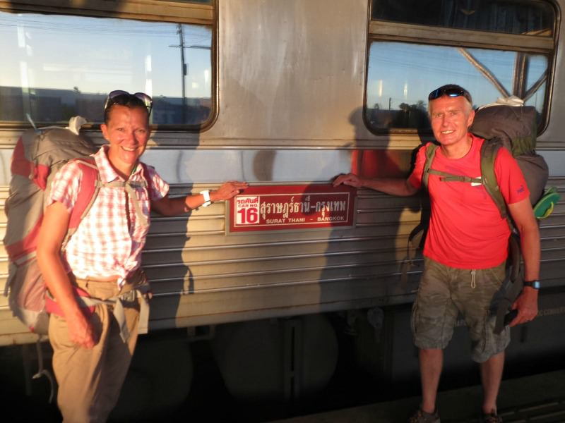 couple standing by train in thailand