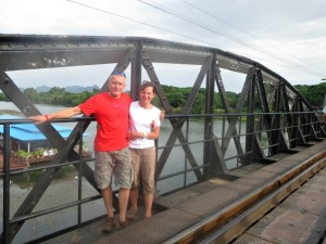 couple standing on metal bridge over kwai river in thailand