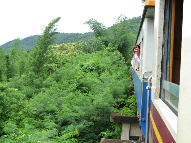 woman looking out of train in the trees in  thailand