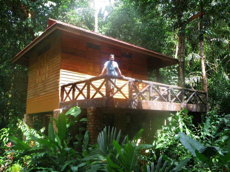 man standing on deck of jungle bungalow in thailand