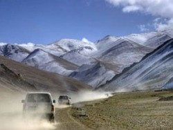 Tibet cars driving toward snow covered mountains