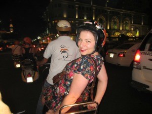 woman riding on scooter through Ho Chi Minh City