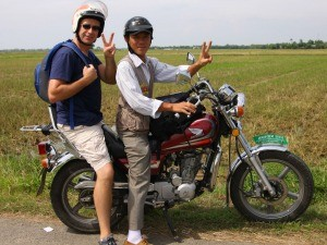 Customer smiling on the back of a bike with local guide