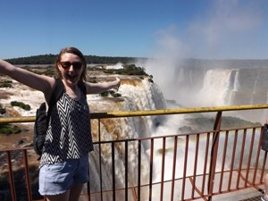 Woman standing with vista of Iguazu Falls in the background in Brazil