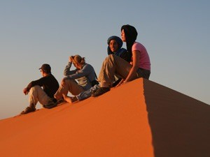 People sitting on a sand dune in Morocco