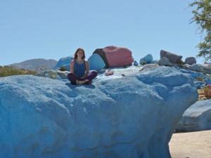 girl sitting on painted blue rock in morocco