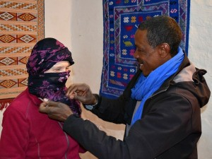 customer with local man tying scarf in morocco