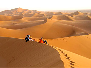 Group of people sitting on a sand dune in the Sahara desert in Morocco