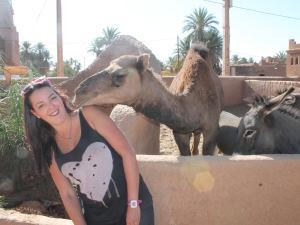 Staff member Sophia standing next to camel in Morocco